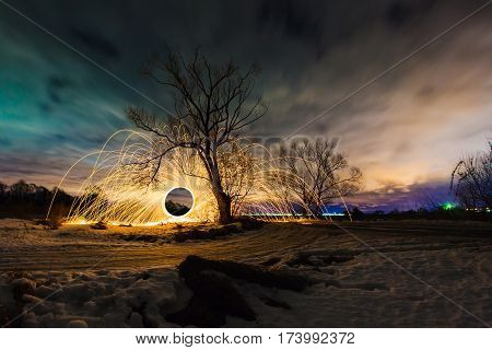 Abstract picture with trajectories of burning sparks near the tree at the background of spring night landscape