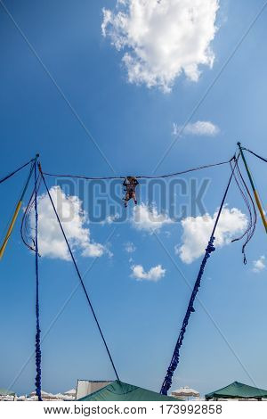 Young girl bungee jump high up in the air with blue sky and clouds. Summer at Sunny beach in Bulgaria.