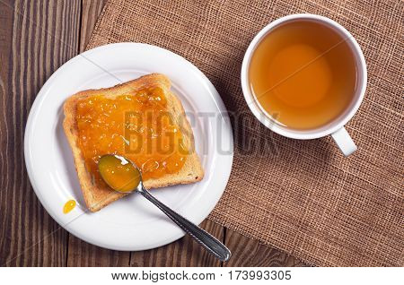 Toasted bread with apricot jam in plate and a cup of black tea on wooden table top view