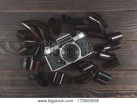 Old camera and films are on the dark wooden surface. Retro. Top view