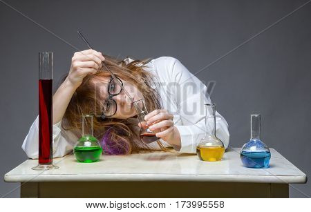 Working shaggy chemist in lab on gray background