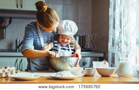 happy family in the kitchen. mother and child daughter preparing the dough bake cookies