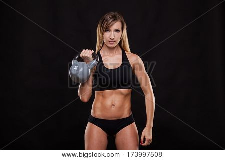 Young attractive fitness woman is doing exercise with a kettlebell workout. Sporty girl showing her well trained body. isolated on dark background with copyspace.