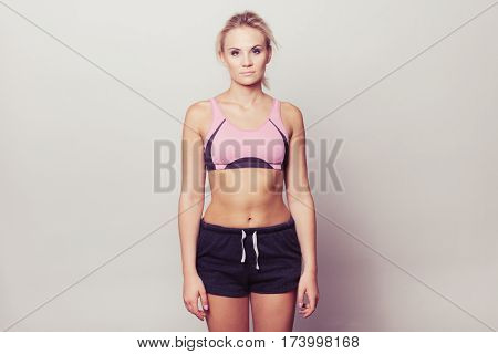 Portrait of sporty fit fitness woman. Attractive girl wearing sporty bra and shorts