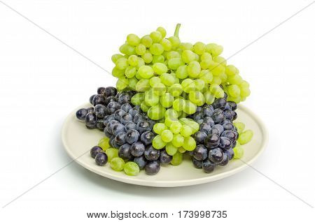 Black and green grapes bunches on white plate isolated on white
