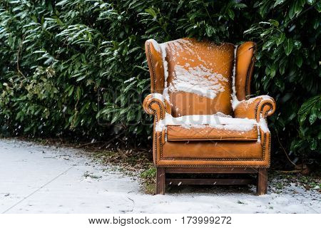 Snow covered seat along the road during snowfall