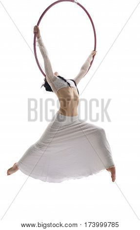 Young pretty brunette in white sexy top and long skirt gracefully perfoming exercises on aerial hoop in studio