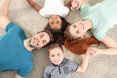 Happy interracial family lying on floor poster