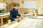 Portrait of a pretty young female carpenter building some furniture in her woodshop poster