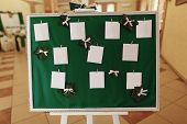 Wedding reception seating plan table guests list on elegant framed board with green cloth and tree leaves with white ribbons in restaurnat hall closeup poster