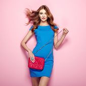Blonde young woman in elegant blue dress. Girl posing on a pink background. Jewelry and hairstyle. Girl with red handbag. Fashion photo poster
