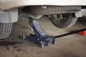 Car Lifted with blue hydraulic floor jack for repairing. poster