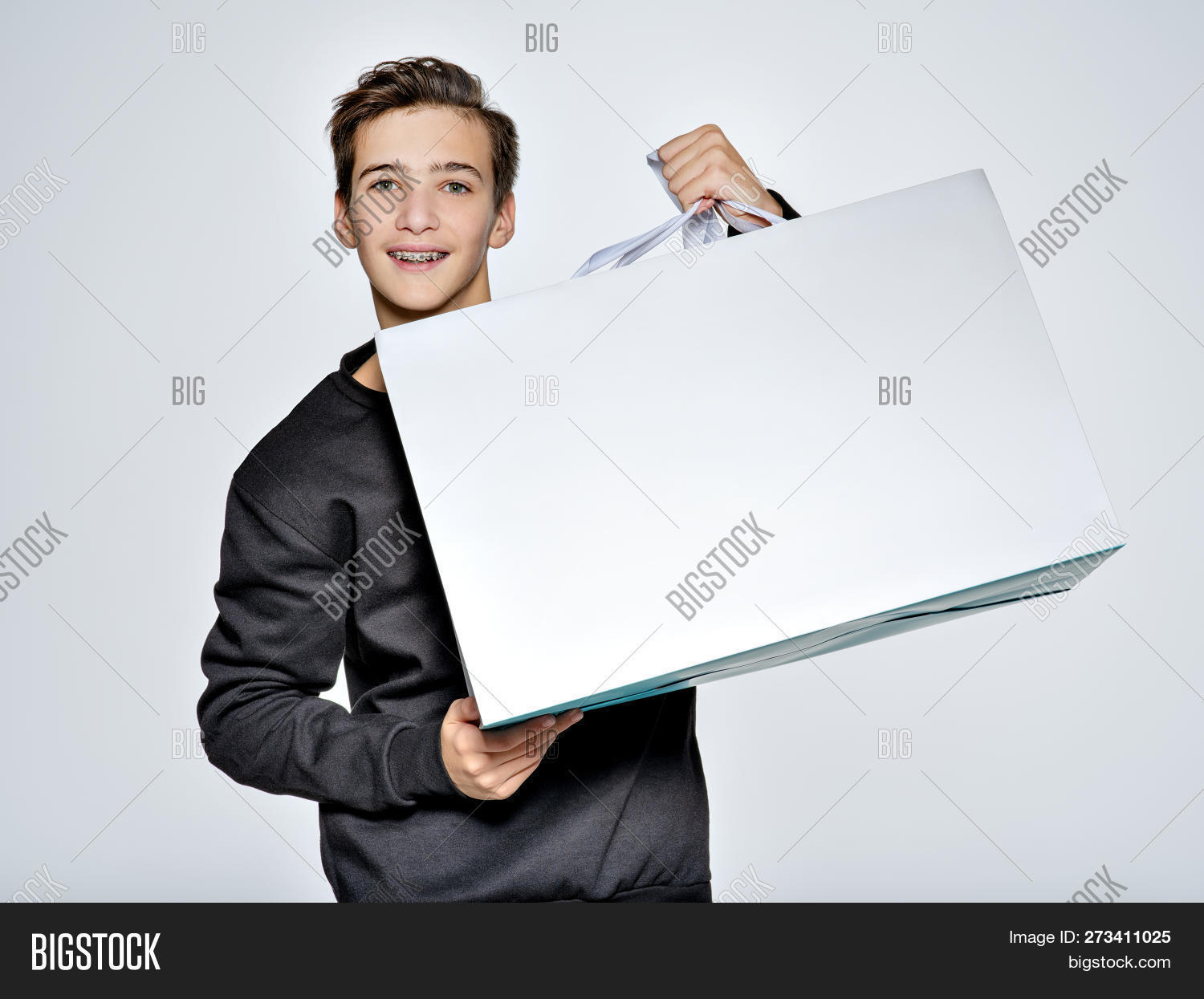 2220d935a Teen boy is pointing by finger to the shopping bag. Teenage boy dressed in  black