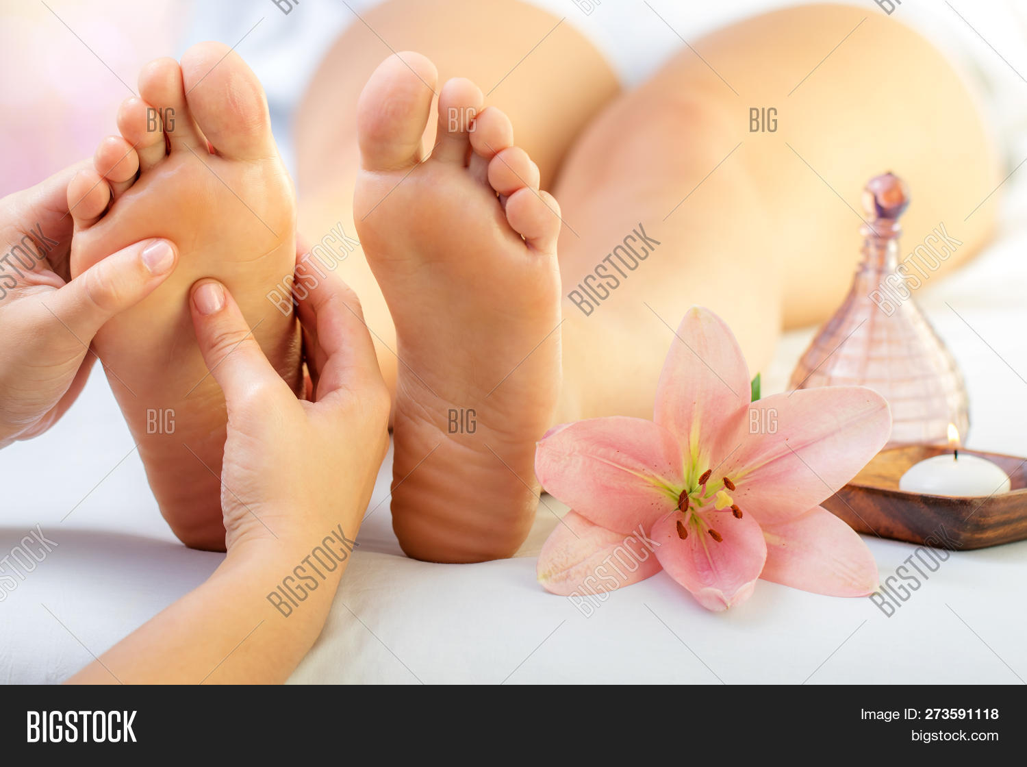 Close up of hands doing foot reflexology massage on female foot. Flower,  candle and massage oil next to feet.
