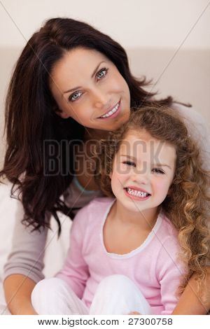 Young mother embracing her daughter