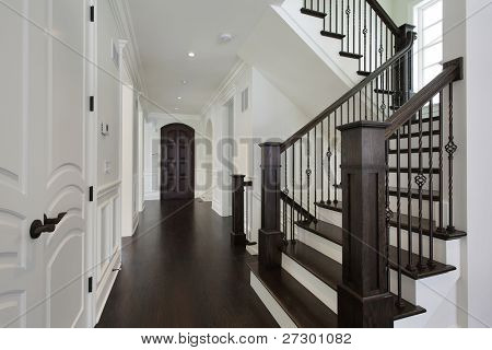 Foyer in new construction home with dark wood staircase