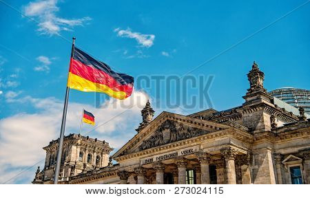 German Flags Waving In The Wind At Famous Reichstag Building, Seat Of The German Parliament Deutsche