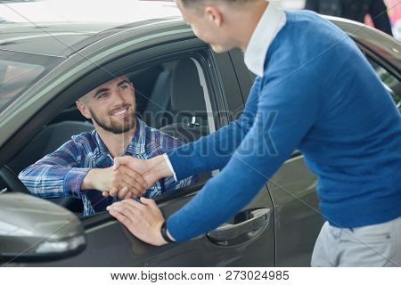 Menager Leaning On Front Door And Shaking Hands With Client After Purchase. Young Man In Blue Sweate