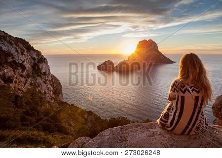 Woman Back To The Front Watching A Beautiful Sunset At The Beach. The Beach Is Called Es Vedra, In I