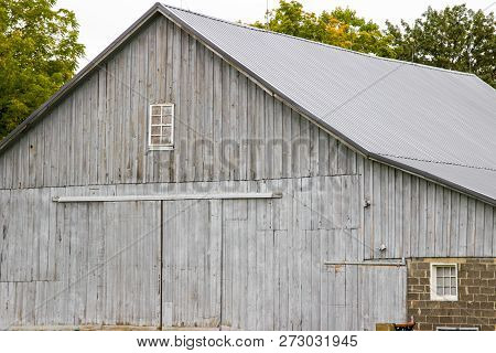 Weathered Rural Barn Background. Grey Weathered Wooden Barn And Barn Door In The Rural American Midw
