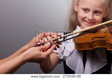 Teacher Shows The Correct Way To Hold The Bow A Little Girl Studying To Play The Violin