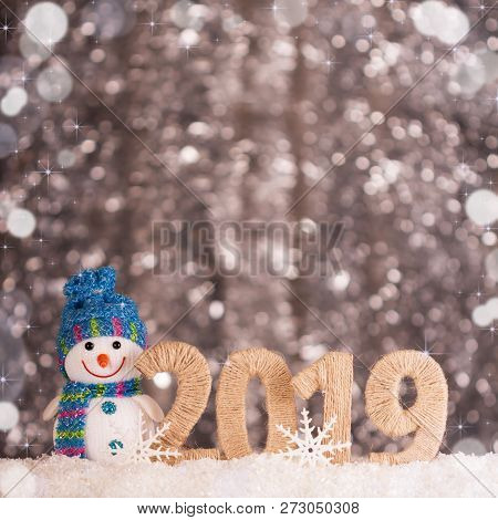 Happy Smiling Snowman And New Year Inscription 2019 On Bright Background With Bokeh Effect