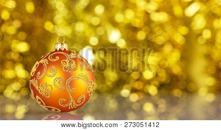Bright Yellow Christmas Ball With Beautiful Decoration On A Yellow Background With Bokeh Effect