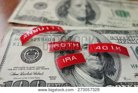 Retirement related labels ( 401k and Roth IRA ) on a hundred dollar bill poster