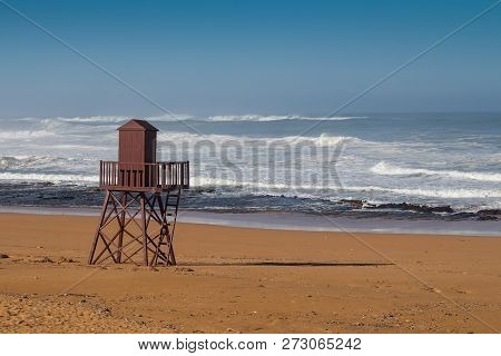 Golden Clean Sand Of The Beach. Wooden Lifeguard Tower. High Tide, Waves With White Foam. Empty Beac