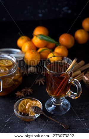 Tea with cinnamon and tangarine marmalade.  Clear glass dish. Dark food photo style. Christmas winter or autumn mood. Homemade citrus cinnamon and anise stars marmalade. Winter family tea poster
