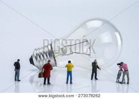 Miniature Figures Near A Light Bulb, Conceptual Image