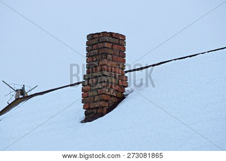 Old Brown Brick Chimney Pipe On The Roof In White Snow
