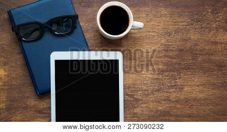 Digital Tablet With Cup Of Coffee, Glasses And Closed Blue Notebook On Wooden Background. Mock Up. S