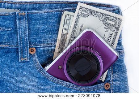 Unknown Compact Camera And Ready Money Are Lying In The Side Pocket Of Blue Jeans.