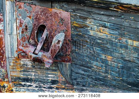 Old Rusty Anchor On A Weathered Wooden Boat With Peeling Paint