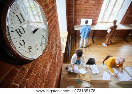 Face of clock hanging on brick wall of modern office where group of casual employees working