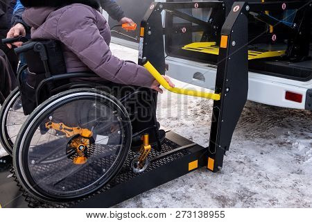 A Man Presses A Button On The Control Panel To Pick Up A Woman In A Wheelchair In A Taxi For The Dis