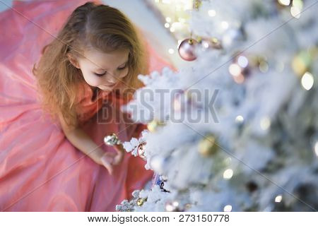 Little Girl At Christmas Decorating Christmas Tree.