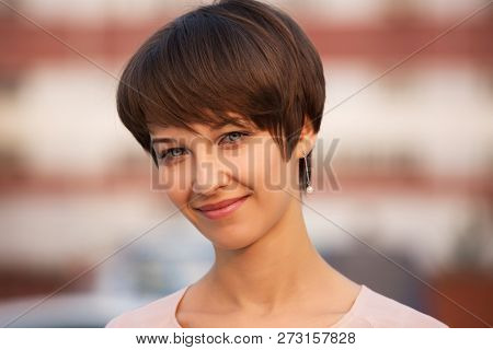 Happy young fashion woman walking on city street Stylish female model with pixie hair