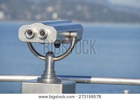 Public Binocular On Sea Shore, Close Up. Coin Operated Binocular Viewer On Blurred Background Of Sun