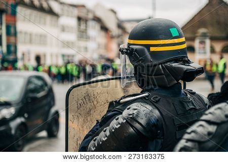 Rear View Of Police Officer Wearing Helmet And Shield Securing The Zone In Frong Of The Yellow Vests
