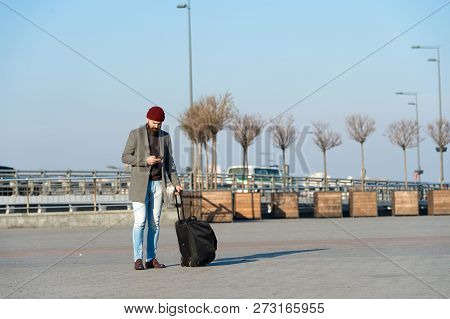 Moving To New City Alone. Man Bearded Hipster Travel With Luggage Bag On Wheels. Traveler With Suitc