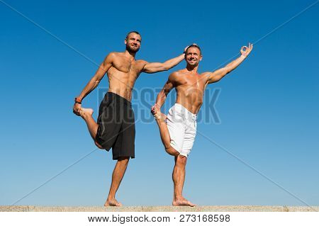 Towards Health. Men Practice Yoga Outdoors. Muscular Men Training On Fresh Air. Reach Balance By Vir