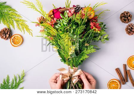 Womens Hands Make A Winter Christmas Bouquet Of Conifers, Roses And Chrysanthemums