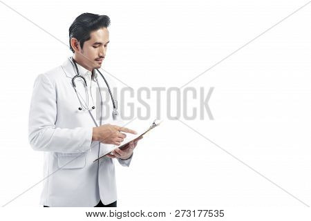 Handsome Asian Doctor Man Wearing Lab Coat Reading Notes On The Clipboard Standing Isolated Over Whi