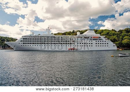 Cruise Ship. Large Luxury White Cruise Ship Liner On Sea Water And Cloudy Sky Background In Fowey. S