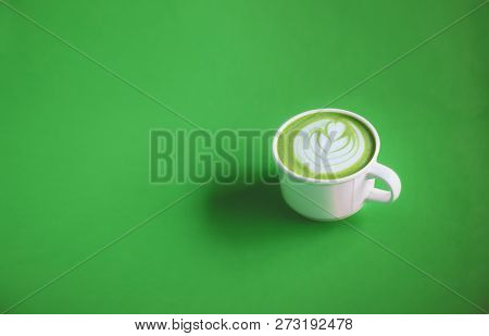 Green Tea Concept, Hot Matcha Green Tea Milk Cream With Art On Top With White Cup On Green Backgroun