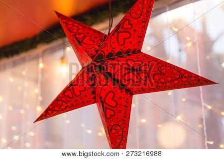 Decorative Red And Black Star Ornament Hanging In A Window With Christmas Lights And Buildings In Ba