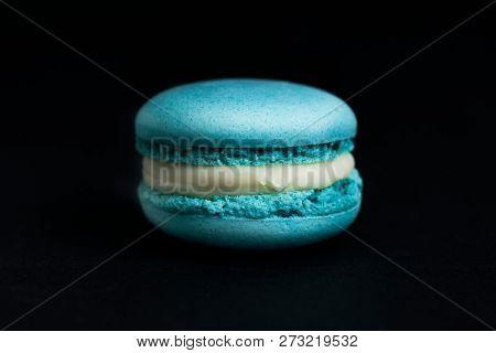 Sweet blue macaroon isolated on black background.