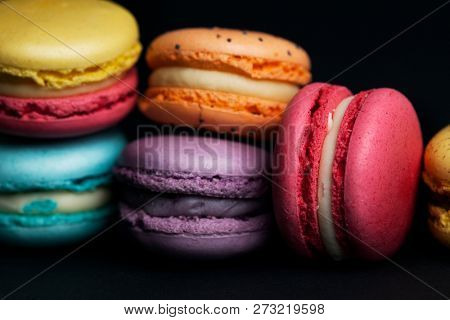 Pile of sweet and colourful french macaroons on black background.